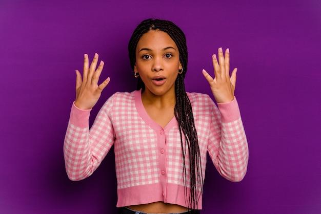 Jeune femme afro-américaine isolée sur fond jaune jeune femme afro-américaine isolée sur fond jaune montrant le numéro dix avec les mains.