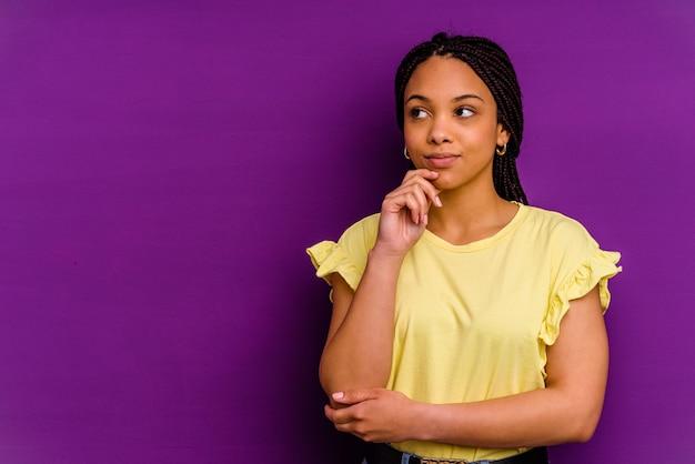 Jeune femme afro-américaine isolée sur fond jaune jeune femme afro-américaine isolée sur fond jaune à la recherche de côté avec une expression douteuse et sceptique.