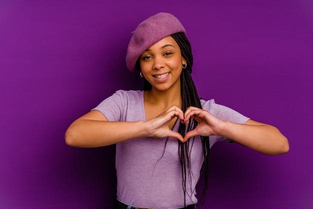 Jeune femme afro-américaine isolée sur fond jaune jeune femme afro-américaine isolée sur fond jaune souriant et montrant une forme de coeur avec les mains.