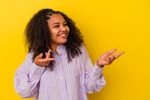 Jeune femme afro-américaine isolée sur fond jaune joyeux riant beaucoup. notion de bonheur.