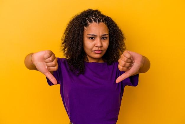 Jeune femme afro-américaine isolée sur fond jaune montrant le pouce vers le bas et exprimant son aversion.