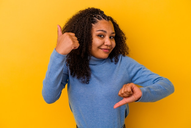 Jeune femme afro-américaine isolée sur fond jaune montrant les pouces vers le haut et les pouces vers le bas, concept difficile à choisir