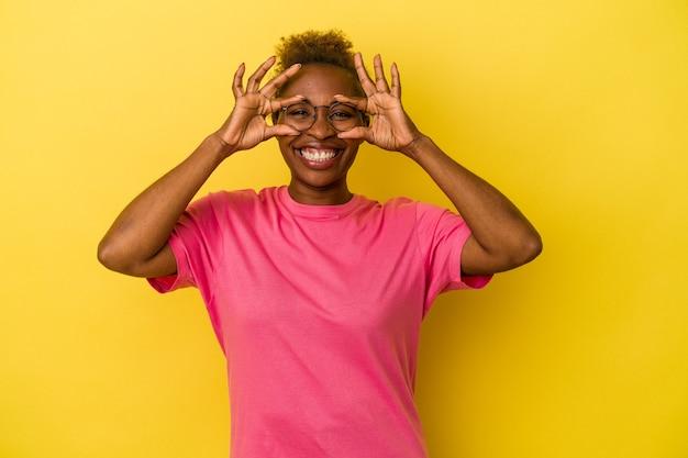 Jeune femme afro-américaine isolée sur fond jaune montrant un signe d'accord sur les yeux