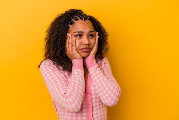 Jeune femme afro-américaine isolée sur fond jaune pleurnichant et pleurant de manière inconsolable.