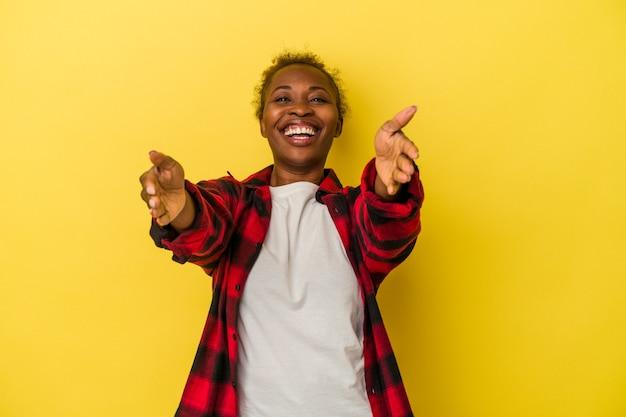 Jeune femme afro-américaine isolée sur fond jaune se sent confiante en donnant un câlin à la caméra.