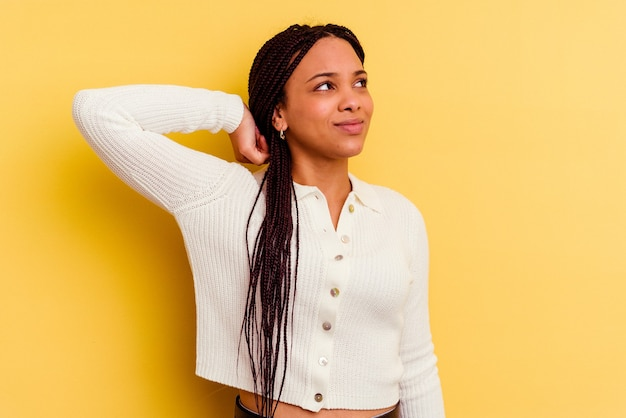 Jeune femme afro-américaine isolée sur fond jaune souffrant de douleurs au cou en raison d'un mode de vie sédentaire.