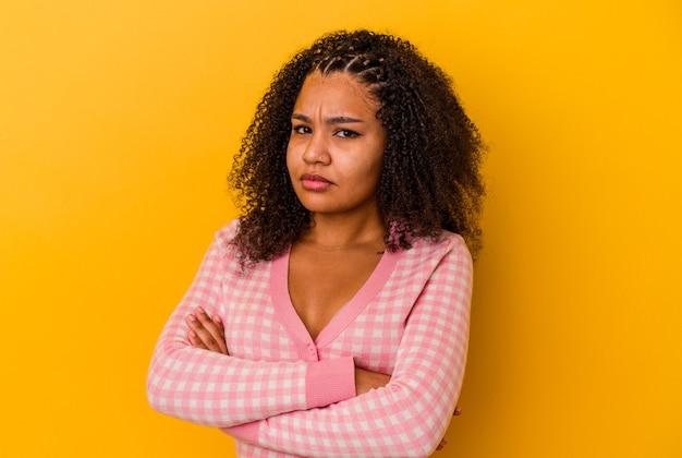 Jeune femme afro-américaine isolée sur fond jaune suspect, incertain, vous examine.