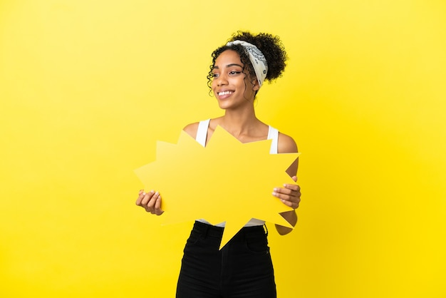 Jeune femme afro-américaine isolée sur fond jaune tenant une bulle de dialogue vide