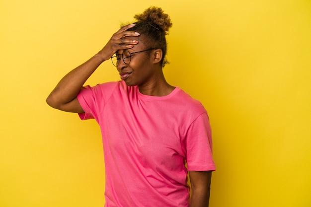 Jeune femme afro-américaine isolée sur fond jaune touchant les temples et ayant des maux de tête.