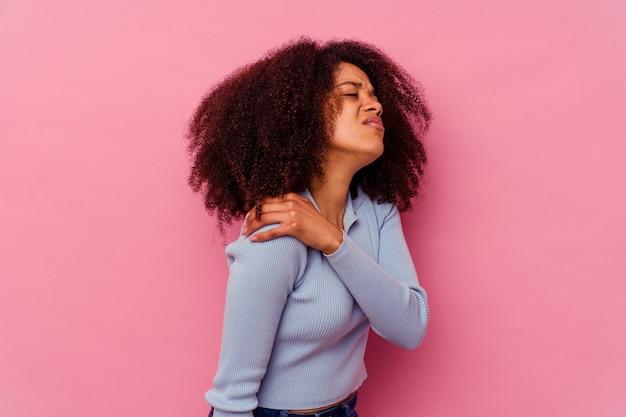 Jeune femme afro-américaine isolée sur fond rose ayant une douleur à l'épaule.