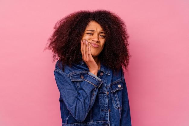 Jeune femme afro-américaine isolée sur fond rose ayant une forte douleur dentaire, mal molaire.