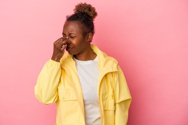 Jeune femme afro-américaine isolée sur fond rose ayant un mal de tête, touchant le devant du visage.