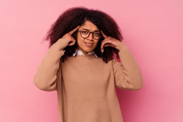Jeune femme afro-américaine isolée sur fond rose concentrée sur une tâche, gardant les index pointant la tête.