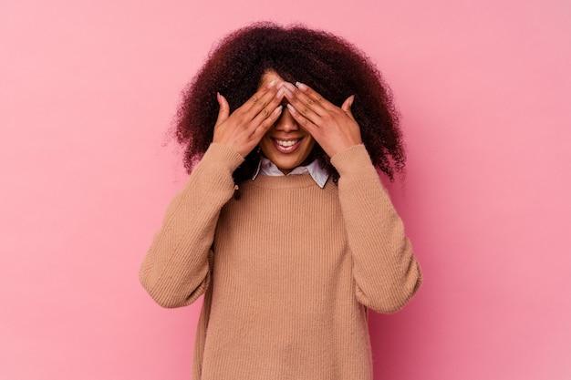 Jeune femme afro-américaine isolée sur fond rose couvre les yeux avec les mains, sourit largement en attente d'une surprise.