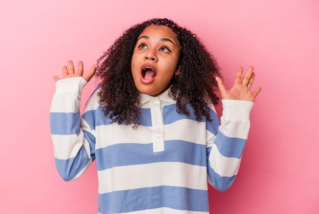 Jeune femme afro-américaine isolée sur fond rose criant vers le ciel, levant les yeux, frustrée.
