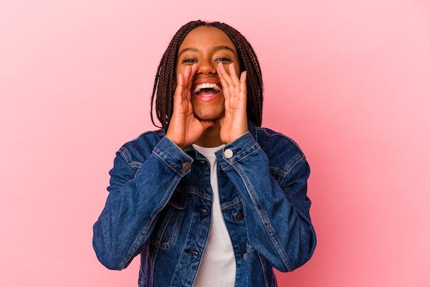 Jeune femme afro-américaine isolée sur fond rose disant un potin, pointant vers le côté rapportant quelque chose.