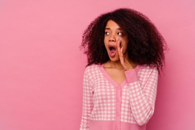 Jeune femme afro-américaine isolée sur fond rose dit une nouvelle secrète de freinage à chaud et regardant de côté