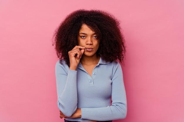 Jeune femme afro-américaine isolée sur fond rose avec les doigts sur les lèvres en gardant un secret.