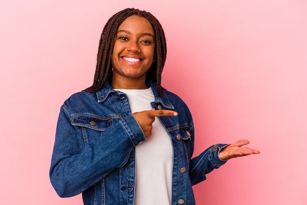 Jeune femme afro-américaine isolée sur fond rose excitée tenant un espace de copie sur la paume.