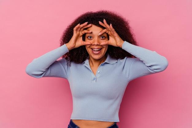Jeune femme afro-américaine isolée sur fond rose en gardant les yeux ouverts pour trouver une opportunité de réussite.