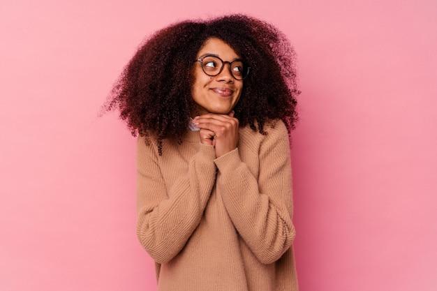 Jeune femme afro-américaine isolée sur fond rose garde les mains sous le menton, regarde joyeusement de côté.