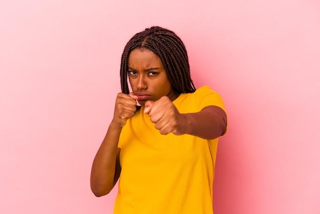 Jeune femme afro-américaine isolée sur fond rose jetant un coup de poing, colère, combat à cause d'une dispute, boxe.