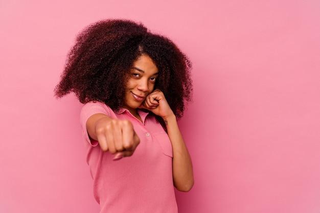 Jeune femme afro-américaine isolée sur fond rose jetant un coup de poing, la colère, les combats en raison d'une dispute, la boxe.