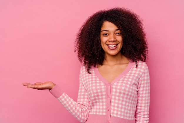 Jeune femme afro-américaine isolée sur fond rose montrant un espace de copie sur une paume et tenant une autre main sur la taille.