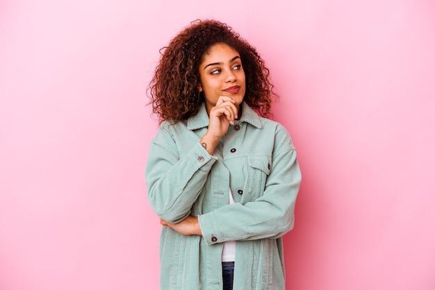 Jeune femme afro-américaine isolée sur fond rose pensant et levant, réfléchissant, contemplant, ayant un fantasme.