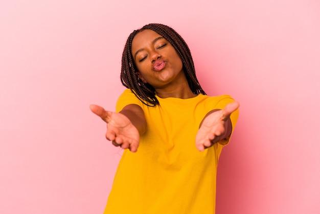 Jeune femme afro-américaine isolée sur fond rose pliant les lèvres et tenant les paumes pour envoyer un baiser aérien.
