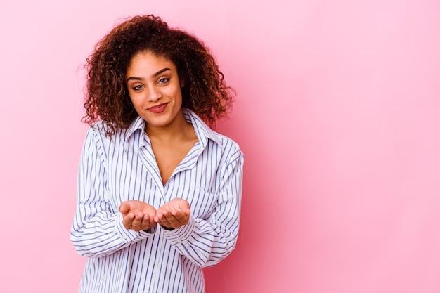 Jeune femme afro-américaine isolée sur fond rose, plier les lèvres et tenant les paumes pour envoyer le baiser de l'air.