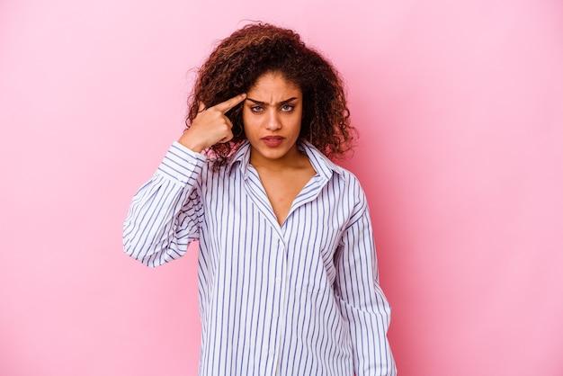 Jeune femme afro-américaine isolée sur fond rose pointant le temple avec le doigt, pensant, concentré sur une tâche.