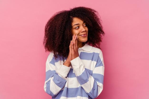 Jeune femme afro-américaine isolée sur fond rose priant, montrant la dévotion, personne religieuse à la recherche d'inspiration divine.