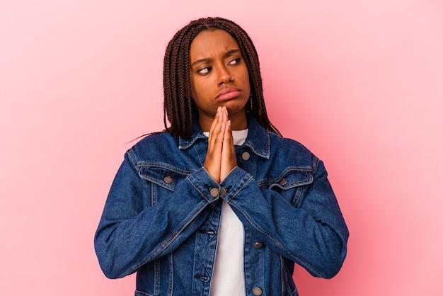 Jeune femme afro-américaine isolée sur fond rose priant, montrant sa dévotion, personne religieuse à la recherche d'une inspiration divine.