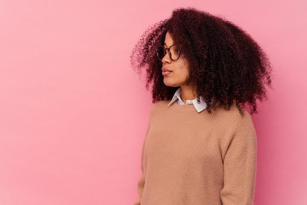 Jeune femme afro-américaine isolée sur fond rose regardant à gauche, pose sur le côté.