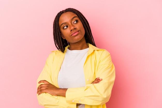Jeune femme afro-américaine isolée sur fond rose rêvant d'atteindre ses objectifs