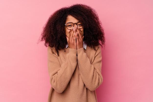 Jeune femme afro-américaine isolée sur fond rose en riant de quelque chose, couvrant la bouche avec les mains.