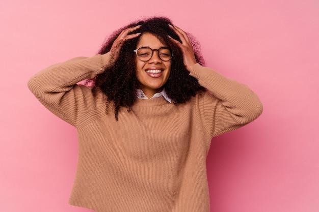 Jeune femme afro-américaine isolée sur fond rose rit joyeusement en gardant les mains sur la tête. notion de bonheur.