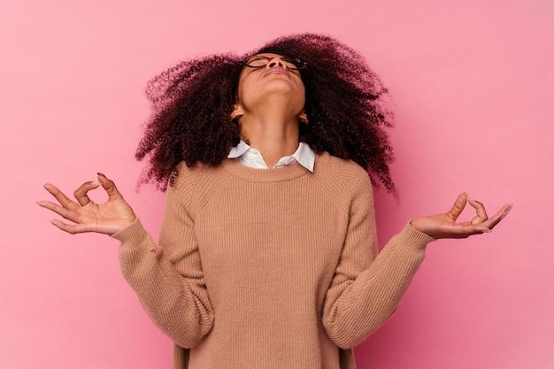 Jeune femme afro-américaine isolée sur fond rose se détend après une dure journée de travail, elle effectue du yoga.