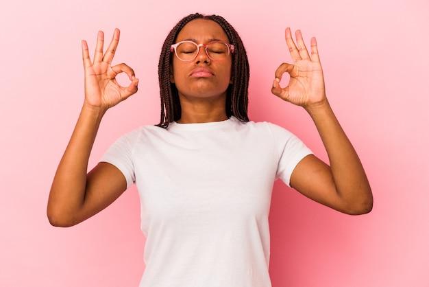 Jeune femme afro-américaine isolée sur fond rose se détend après une dure journée de travail, elle fait du yoga.