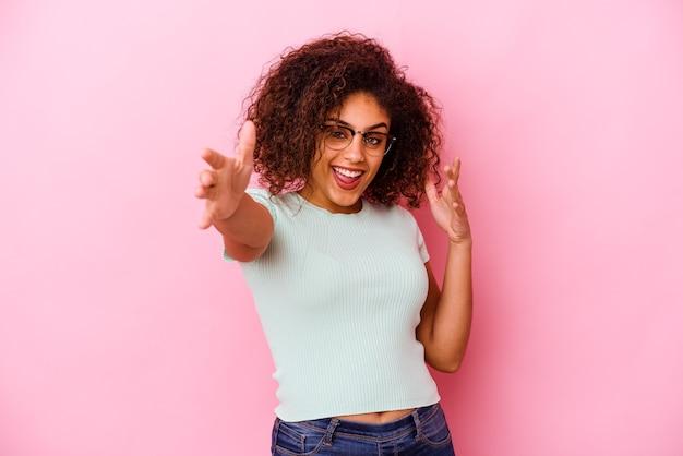 Jeune femme afro-américaine isolée sur fond rose se sent confiant en donnant un câlin à la caméra.