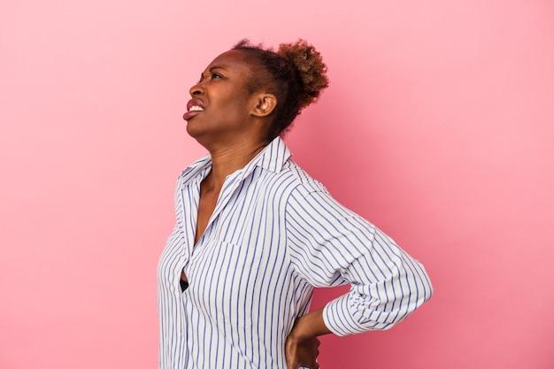 Jeune femme afro-américaine isolée sur fond rose souffrant d'un mal de dos.