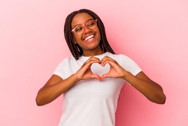 Jeune femme afro-américaine isolée sur fond rose souriant et montrant une forme de coeur avec les mains.
