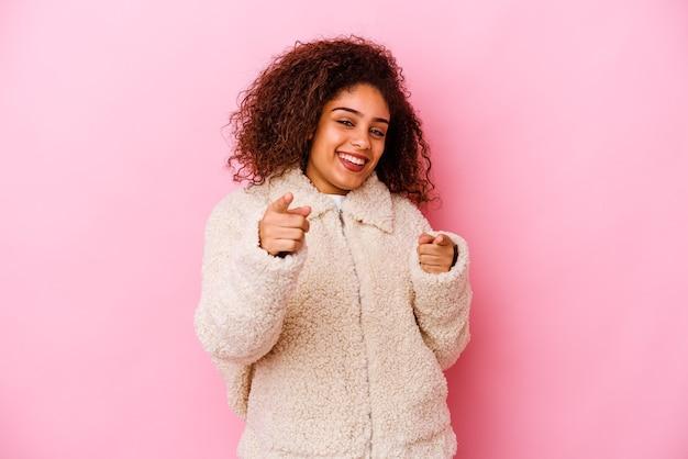 Jeune femme afro-américaine isolée sur fond rose sourires joyeux pointant vers l'avant.