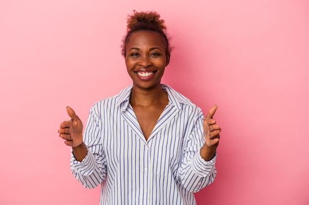 Jeune femme afro-américaine isolée sur fond rose tenant quelque chose à deux mains, présentation du produit.