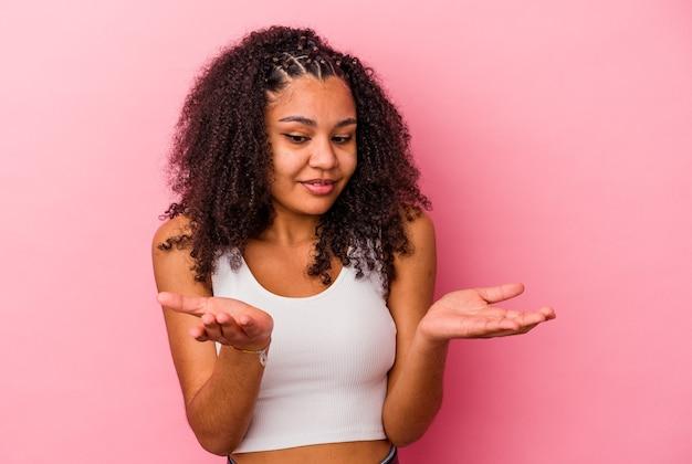 Jeune femme afro-américaine isolée sur fond rose tenant quelque chose avec des paumes, offrant à la caméra.