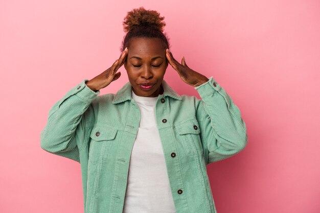 Jeune femme afro-américaine isolée sur fond rose touchant les temples et ayant des maux de tête.