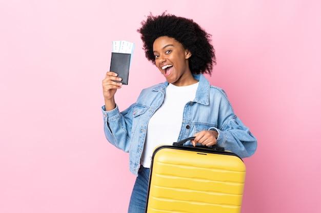 Jeune femme afro-américaine isolée sur fond rose en vacances avec valise et passeport