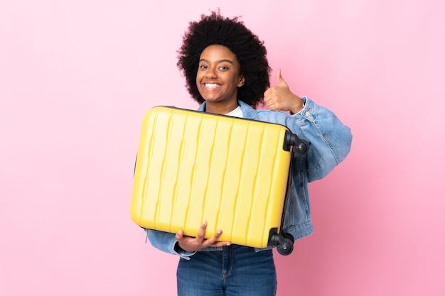 Jeune femme afro-américaine isolée sur fond rose en vacances avec valise de voyage et avec le pouce vers le haut