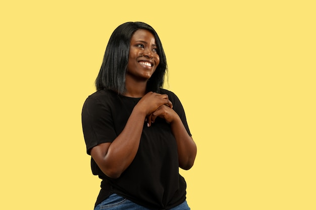 Jeune femme afro-américaine isolée sur fond de studio jaune, expression faciale. beau portrait de femme en demi-longueur. concept d'émotions humaines, expression faciale. debout et souriant.